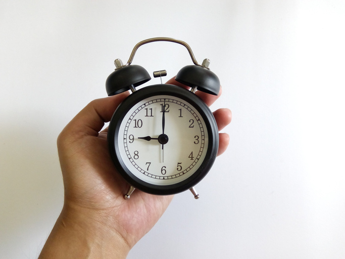 cambio de horario mano sosteniendo a un reloj de manecillas