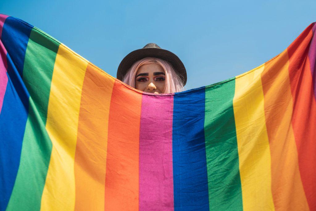 Mujer con bandera del orgullo gay sonriendo